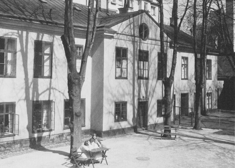 Åsö sjukhus i bakgrunden med två kvinnor på bänk framför - träd