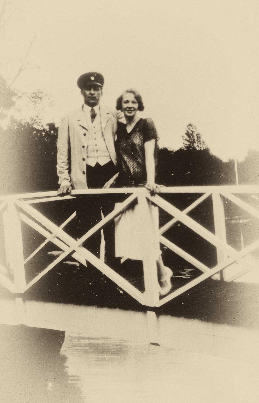 En man och en kvinna håller om varandra stående på sjukhusdammens bro.