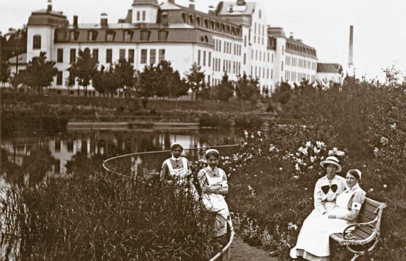 Sjukhuspersonal på bänk framför sjukhusets damm