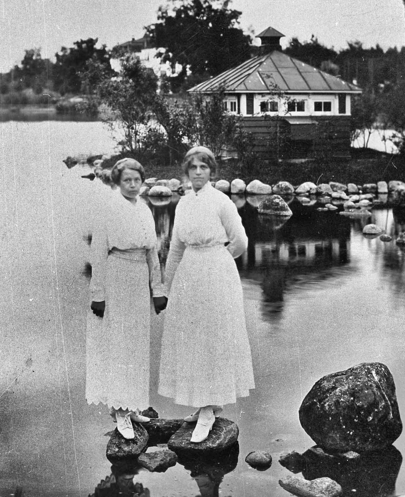Två kvinnliga vårdbiträden står på stenar i sjukhusdammen med svanhuset i bakgrunden